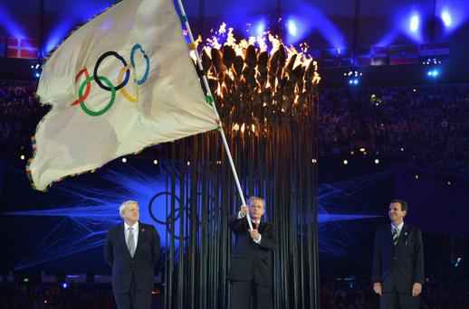 President of the International Olympic Committee Jacques Rogge holds the Olympic flag after receiving it from London Mayor Boris Johnson (L), before passing it to Rio de Janeiro Mayor Eduardo Paes (R) during the ceremonial handing over of the Olympic flag at the closing ceremony of the London 2012 Olympic Games at the Olympic stadium August 12, 2012. REUTERS/Jeff J Mitchell/Pool (BRITAIN - Tags: POLITICS SPORT OLYMPICS)