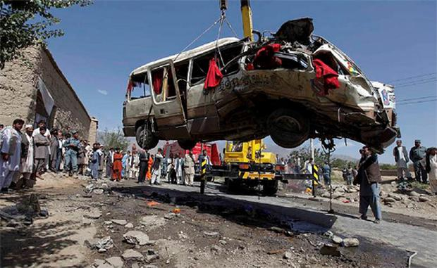 Afghan villagers look on as a crane hoists away the wreckage of a civilian bus, which was hit by a remote-controlled bomb, in the Paghman district of Kabul August 7, 2012.