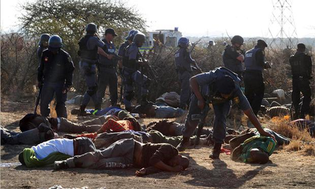 Police surround the bodies of striking miners after opening fire on a crowd at the Lonmin Platinum Mine near Rustenburg, South Africa, Thursday, Aug. 16, 2012.