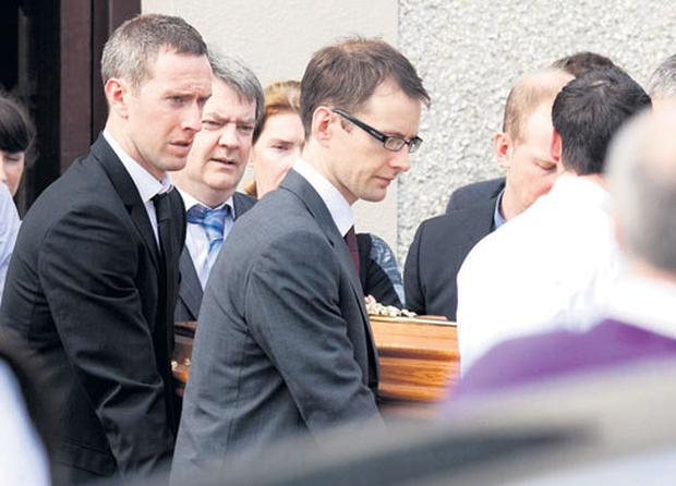 Tipperary hurler John O'Brien (left, in black suit) helps carry the coffin of his brother Thomas O'Brien. PRESS 22