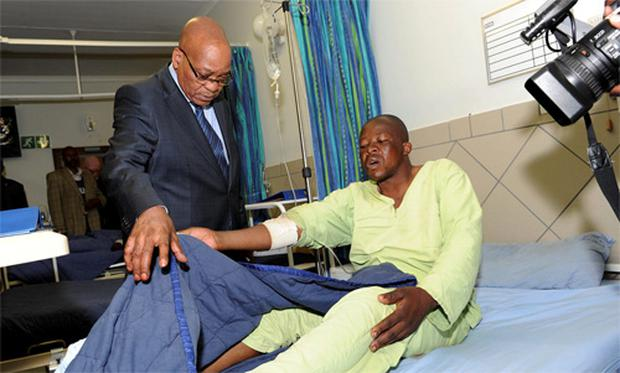 South Africa's President Jacob Zuma (L) chats with one of the injured miners during a courtesy visit in a hospital outside a South African mine in Rustenburg, 100 km (62 miles) northwest of Johannesburg, August 17, 2012.