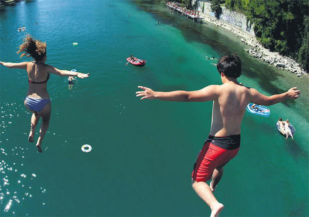 People jump from a bridge into the Rhone river at the Jonction on a hot sunny summer day in Geneva yesterday.