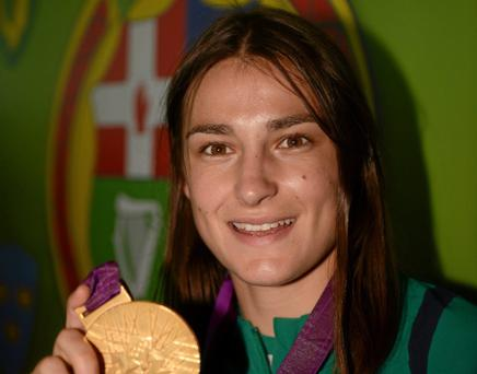 13 August 2012; Olympic champion Katie Taylor celebrates with her gold medal for boxing on their arrival home from the London 2012 Olympic Games. Dublin Airport, Dublin. Picture credit: Ray McManus / SPORTSFILE