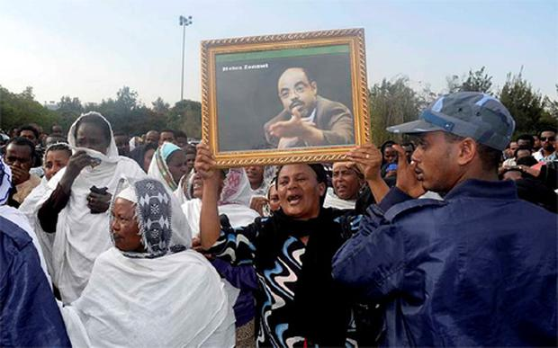 A woman cries while lifting a portrait of Ethiopia's Prime Minister Meles Zenawi as she waits for the arrival for his remains in Ethiopia's capital Addis Ababa August 21, 2012.