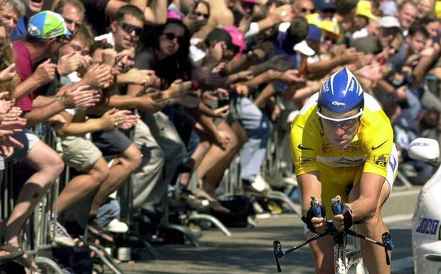 Yellow jersey Lance Armstrong of the US is cheered by enthusiastic fans as he speeds pass during the 19th stage of the Tour de France 2000