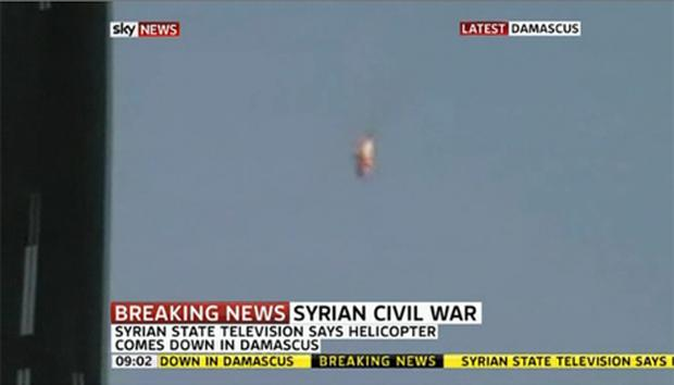 Grainny footage of what appears to be a Syrian helicopter in flames