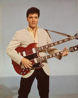 Portrait of American singer and actor Elvis Presley (1935 - 1977) as he holds a twelve string guitar, mid 1950s . (Photo by Hulton Archive/Getty Images)