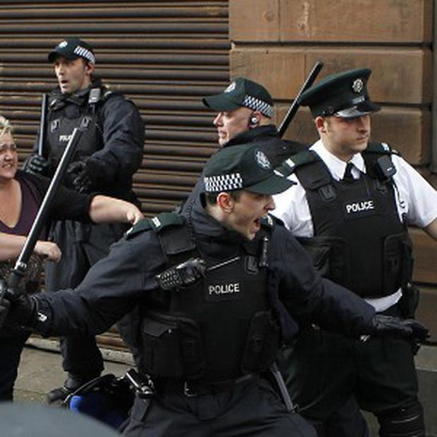 Police officers attempt to stop fighting between loyalist and nationalist groups outside outside St Patrick's Roman Catholic Church in Belfast (AP)