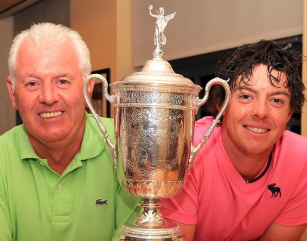 Rory McIlroy and his father Gerry McIlroy pose with the trophy after his eight-stroke victory during the 111th U.S. Open at Congressional in 2011