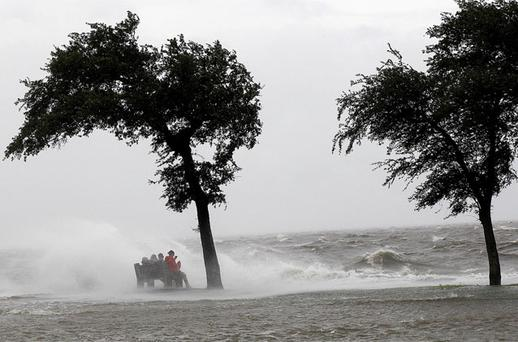 People sit on a bench along the seawall in the storm surge from Isaac, on Lakeshore Drive along Lake Pontchartrain, as the storm approaches landfall, in New Orleans