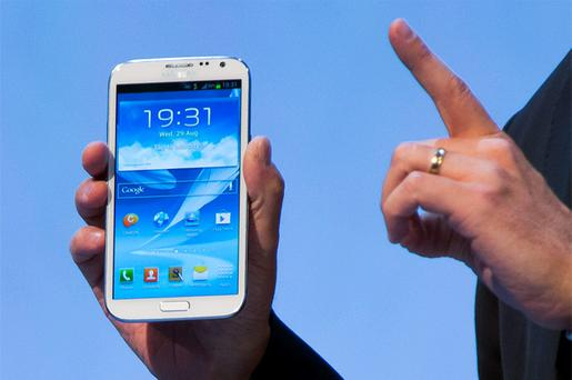 A man presents the new Samsung Galaxy Note II smartphone during the Samsung Mobile Unpacked event in Berlin