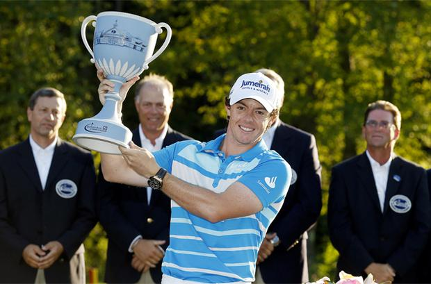 Rory McIlroy, of Northern Ireland, holds the trophy after winning the Deutsche Bank Championship PGA golf tournament
