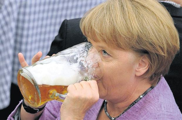 German Chancellor Angela Merkel drinks beer in a beer tent during a fair in Abensberg, southern Germany, yesterday