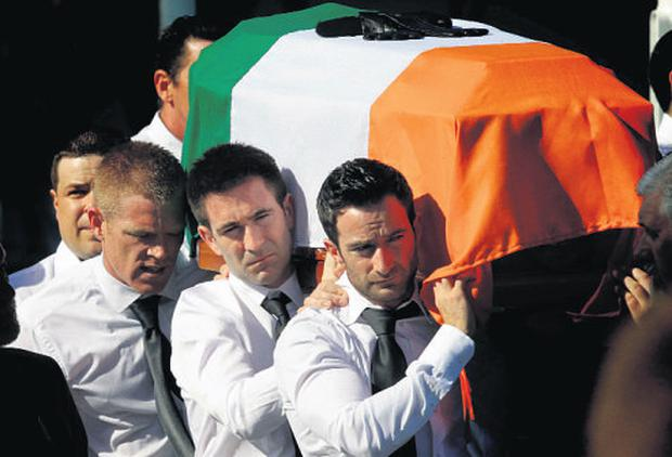 Mourners carrying the coffin of Alan Ryan