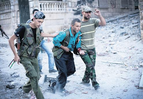 Soldiers with the Free Syrian Army help a wounded fighter after he was shot by army forces in Aleppo, Syria