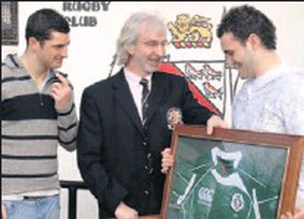 John Whately, President Dundalk Rugby Club, being presented with Ireland jerseys by Robert (Left) and David Kearney at Dundalk Rugby Club last year.
