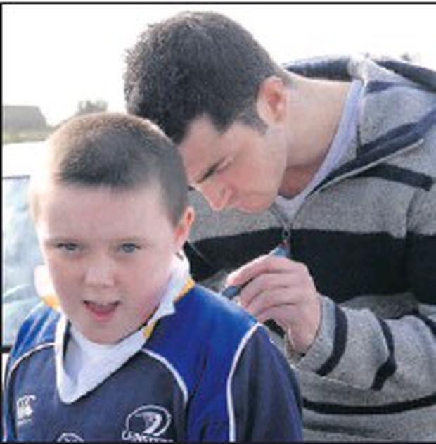 Lucky Stephen Arrowsmith gets his Leinster jersey signed by Robert Kearney during a visit to Dundalk Rugby Club last year.