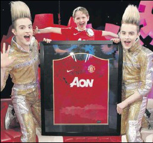 Luka Murphy shows Jedward the signed jersey he got from his favourite team, Manchester United.