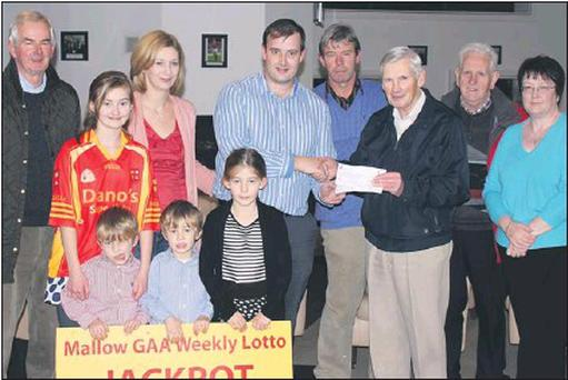 Mallow GAA lotto jackpot winner Alan Sheehan with his wife Caroline children Katie, Emily, Eoin and Mark. Also pictured is Club Treasurer Seán Ryan, winning lotto ticket seller Tom O'neil and Mallow GAA lotto Committee Bill O'malley and lotto...