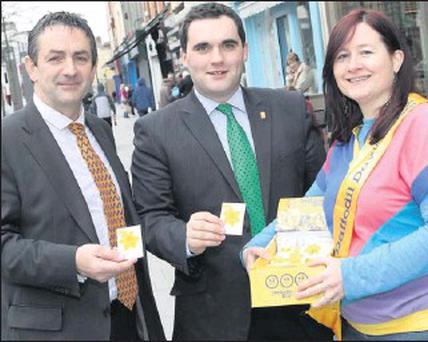 Cllr Richie Culhane and Mayor Kevin Callan buying a pin from Maureen Kelly on Daffodil Day.