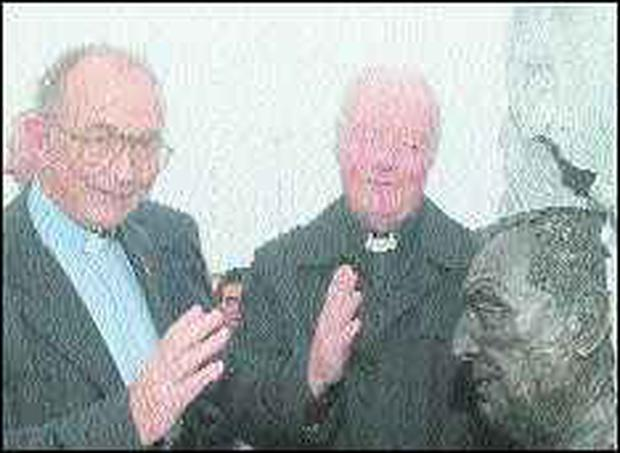 Dingle parish priest Monsignor Pádraig Ó Fiannachta, left, and Fr Eoghan Haughey, brother of the former taoiseach, bless the bronze relief image of Charles Haughey on Dingle pier on Sunday.
