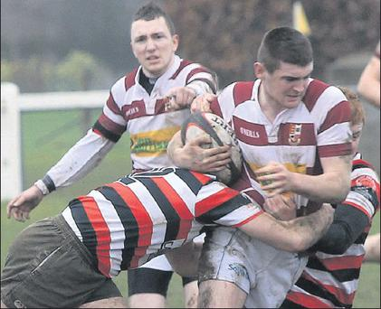 Tullow's Stephen Nolan is stopped in his tracks by two Enniscorthy tacklers.
