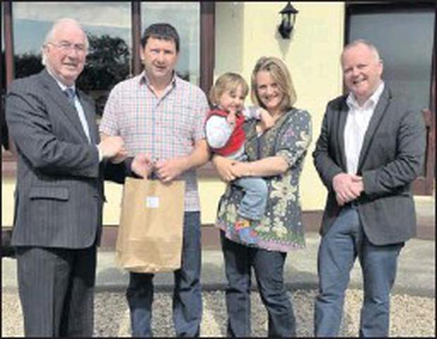 Brendan Halligan chairman of SEAI and Tomás O'Leary, managing director of Mos Art present Sean and Allison Cooney and Joseph from Ballinacoola, Glenealy, with their Efficiency report, from the Ballynagran Engery Plus Community.