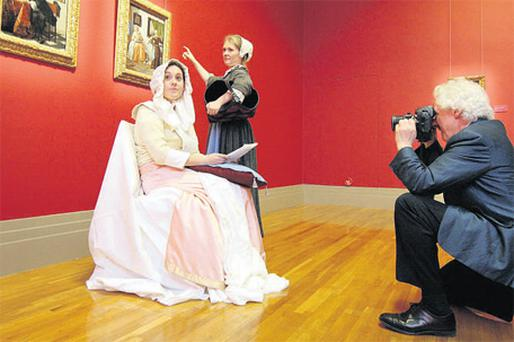 Raymond Keaveney, director of the National Gallery of Ireland, takes a photo of Aisling Jones and Emma Smith, posing as the subjects of Dutch master Gabriel Metsu's famous work 'A Woman Reading a Letter'