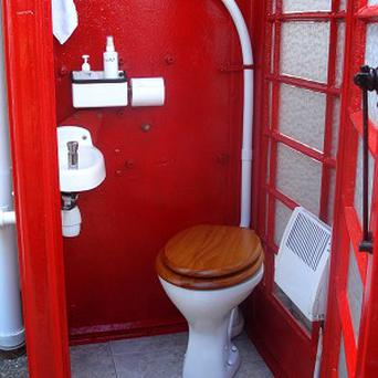 An old red phone box which has been turned into a toilet