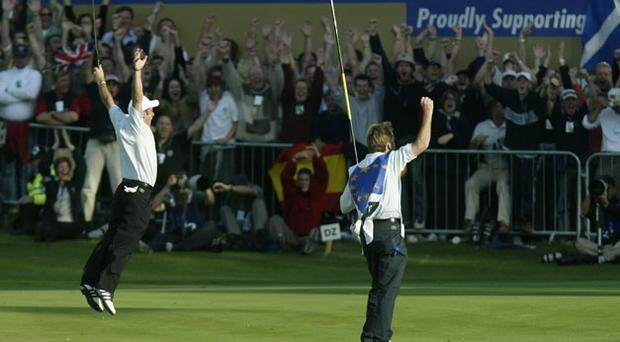 Paul McGinley celebrates after holing his par putt on the 18th green to halve his match against Jim Furyk in the final day singles and secure victory for Europe in the 34th Ryder Cup. Photo: Getty Images