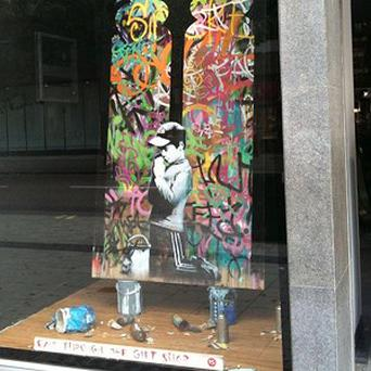 A Banksy painting was placed in the window of HMV's branch in London's Oxford Street