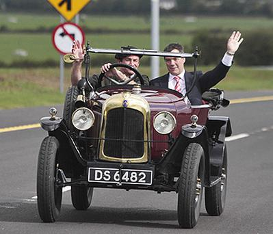 Transport Minister Noel Dempsey (right) as he is driven down a new 40km section of the M9 motorway from Carlow to Knocktopher in a 1922 citron C5 by local man Michael Power. Photo: PA