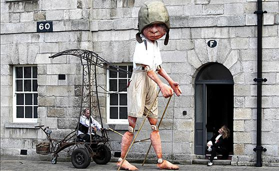 Macnas performer Debbie Wright is dwarfed by the 15-foot puppet that stalked around the National Museum of Ireland, Collins Barracks, Dublin, yesterday