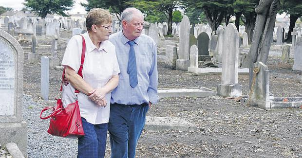 Former Bethany Home resident from 1941 to 1945 Derek Leinster and his wife Carol beside unmarked graves at Mount Jerome