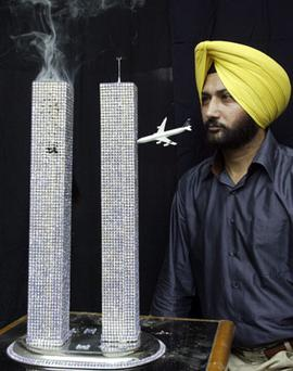 MEMORIAL: Artist Harwinder Singh Gill with a model of the World Trade Centre under attack in the north Indian city of Amritsar. Gill made the model as a tribute to the people who lost their lives during the September 11 attacks, on the eve of the anniversary of the attacks.