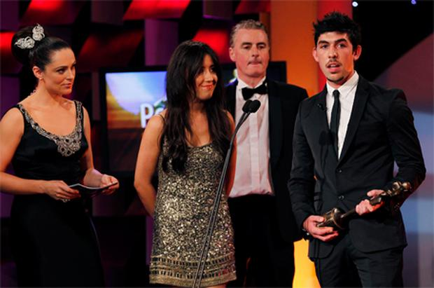 Lottie and Rex Ryan on stage with Grainne Seoige and Dave Fanning as they received an award on behalf of their father, Gerry Ryan, at the People of the Year Awards 2010, in Dublin