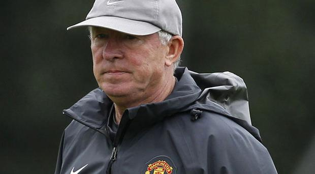 Manchester United manager Alex Ferguson watches his players during a training session at the club's Carrington complex yesterday. Photo: Reuters