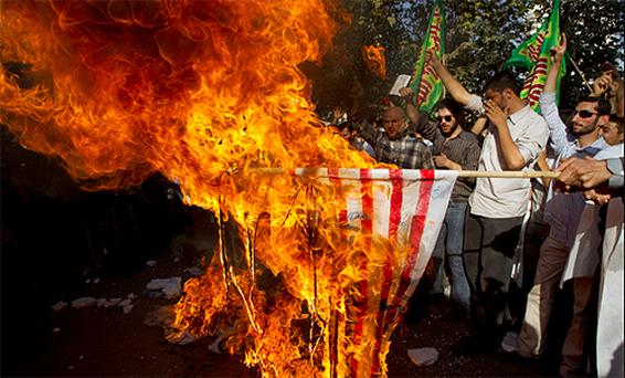 Demonstrators burn an American flag in Tehran to protest plans by a US pastor to burn the Koran