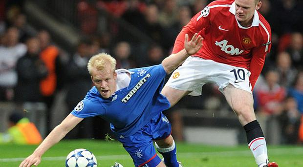 Rangers' Steven Naismith falls as Wayne Rooney challenges him for the ball at Old Trafford last night. Photo: PA