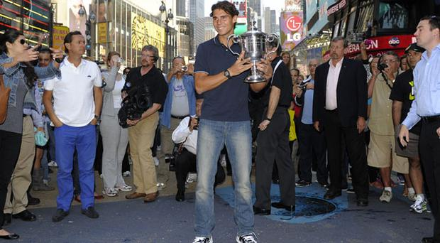Passers-by take their photographs as Rafael Nadal poses with the US Open trophy in New York's Times Square yesterday following his victory over Novak Djokovic. Photo: Getty Images
