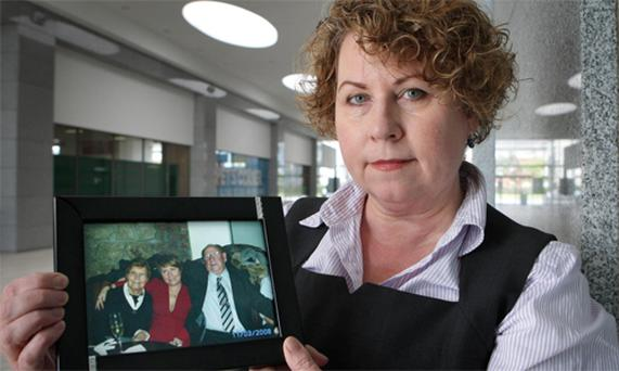 Bernie Traynor holds a picture of herself with her dad, Kevin and mother Bridget after the inquest yesterday. Photo: Frank McGrath
