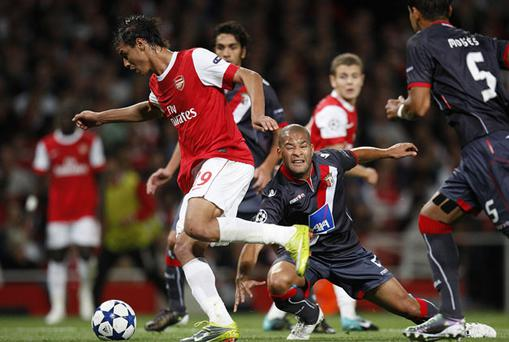 Marouane Chamakh (left) runs through the Braga defence on his way to scoring Arsenal's third goal. Photo: PA
