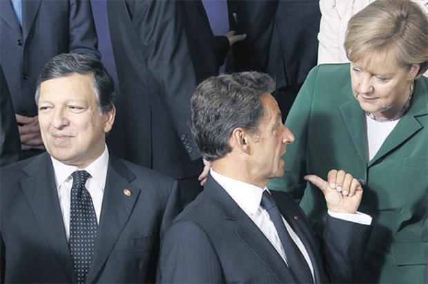 French President Nicolas Sarkozy talks to German Chancellor Angela Merkel as they pose for a photo with European Commission President Jose Manuel Barroso (left) during the European Union leaders' summit in Brussels yesterday