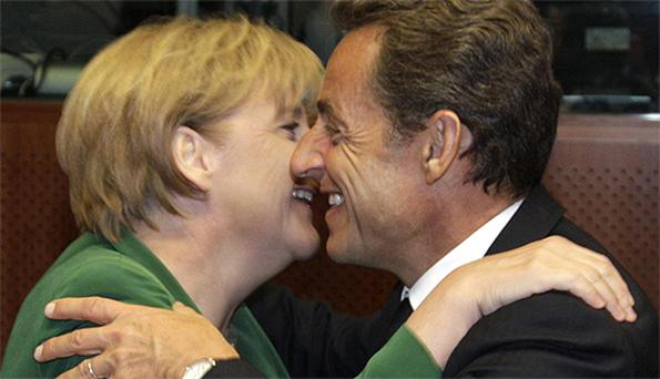 French president Nicolas Sarkozy embraces German chancellor Angela Merkel at the European Union summit in Brussels