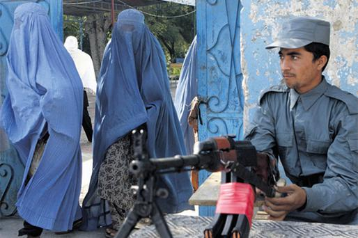 READY: An Afghan policeman keeps watch as women arrive at a polling station in Jalalabad yesterday