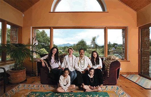 Romio, his wife Sophie and their four daughters in their living room. On the couch, from left, are Amber and Topaz, while Metta and Jaya are seated on the floor. After years as an artist, Romio now hopes to spread his message of peace through seminars, meditation and healing sessions