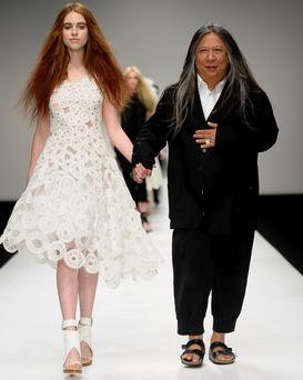John Rocha with a model wearing a dress from his spring/summer 2011 collection. Photo: Getty Images