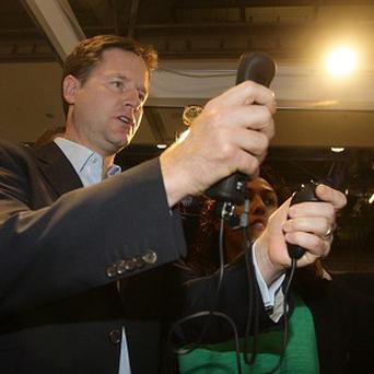 Nick Clegg plays an archery game at the Liberal Democrats' annual conference in Liverpool