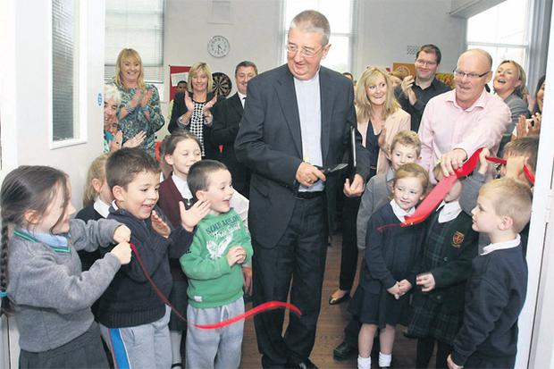 Archbishop Martin opens the Wellington Street centre in Dublin yesterday. The centre is an old school that has been completely revamped into a support service for young people who have left residential or foster care. The centre will also be used for an after-school project for local children, some of whom helped the bishop cut the red tape