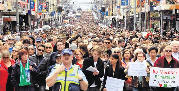A police officer leads 30,000 marchers along Melbourne's Sydney Road yesterday as citizens turned out in force to remember murdered Irish woman Jill Meagher
